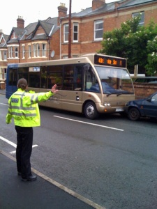 Policewoman directs traffic after driverless Fiesta crashes into bus.